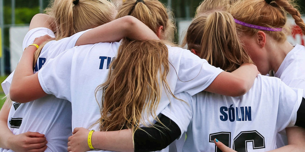 Group of football girls holding each others during a match